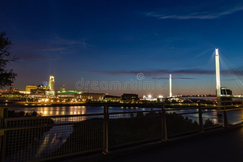 Omaha Nebraska downtown skyline at dusk. Bob Kerrey foot bridge over Missouri river. stock image
