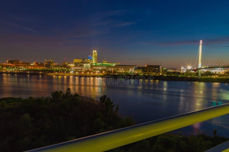 Omaha Nebraska w centrum linia horyzontu przy półmrokiem Bob Kerrey stopy most nad Missouri rzeką zdjęcia stock