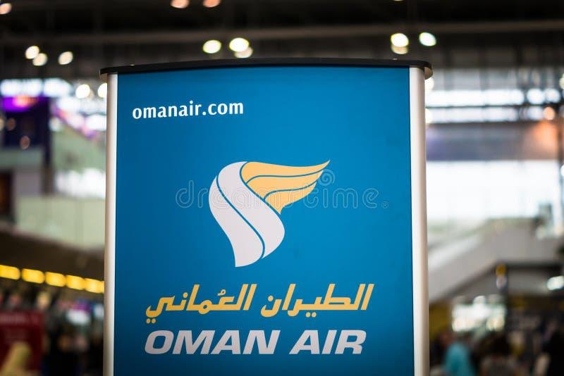 Oman Air-embleem bij incheckbalie stock afbeeldingen
