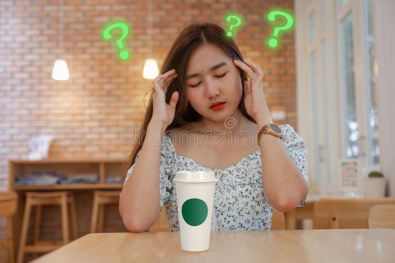 Oman confuse with coffee cup or ice coffee. Asian woman confuse with coffee cup or ice coffee royalty free stock photo