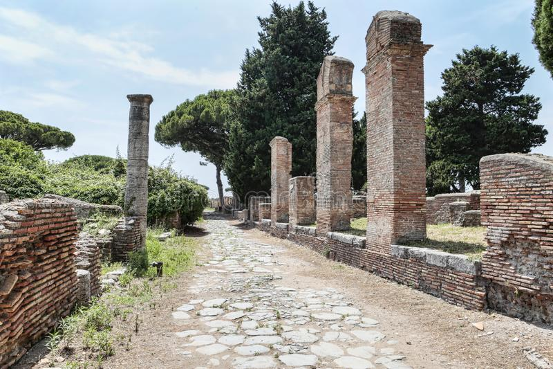 Roman empire street view with ruins and roman columns and typical cobblestone road at Ostia Antica - Rome. Italy royalty free stock photography