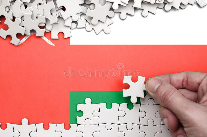 Oman flag is depicted on a table on which the human hand folds a puzzle of white color stock image