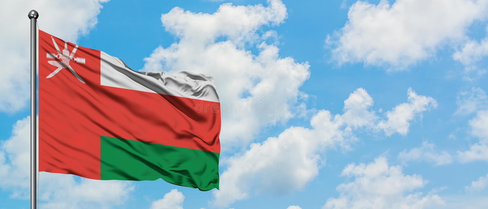 Oman flag waving in the wind against white cloudy blue sky. Diplomacy concept, international relations.  stock photos
