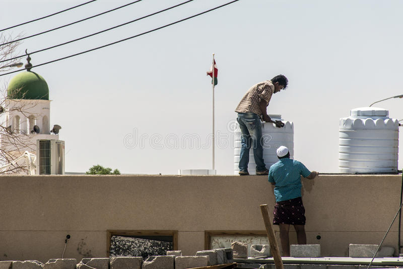 Oman Salalah 17.10.2016 People working in front of Mosque tower ubar Dhofar mountain region flag stock photos