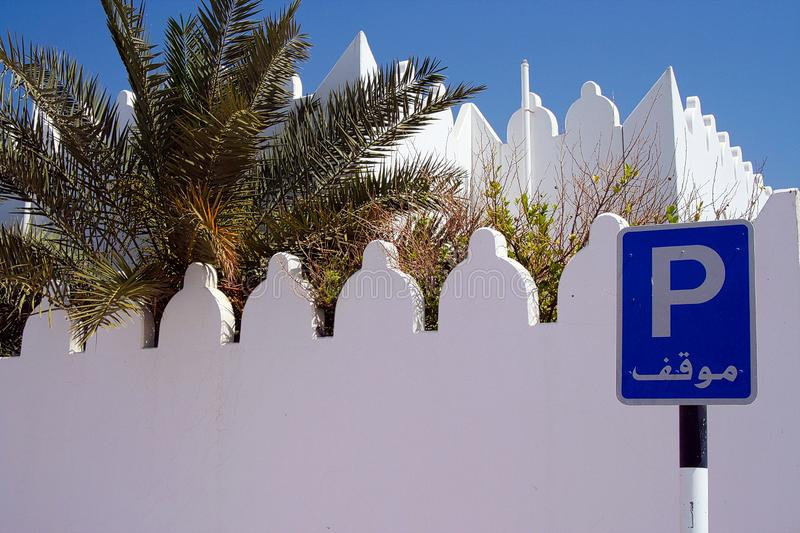 View on  blue parking sign with white battlement wall and palm tree, Oman royalty free stock photo