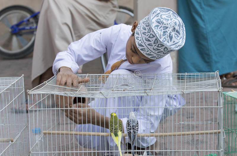 omani boy with a bird cage stock image