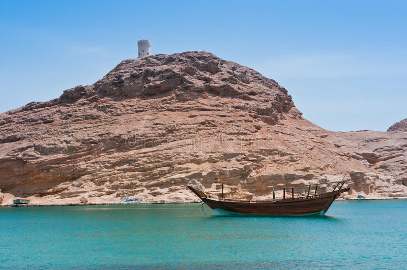 Omani Coastline. The rocky and mountainous coastline of Oman, with an abandoned watchtower in the distance and a typical dhow in the water stock photography