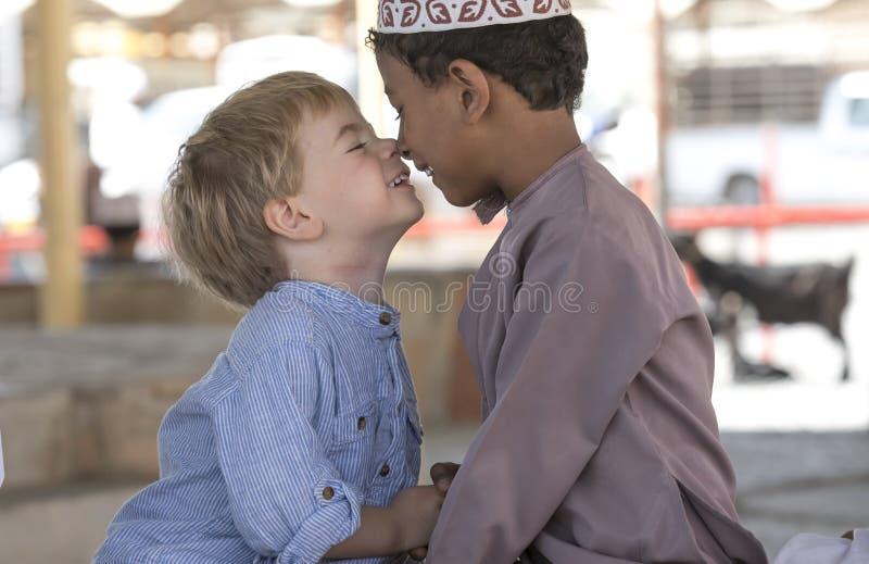 Omani jongen die frineds met Europese jongen maken royalty-vrije stock afbeelding