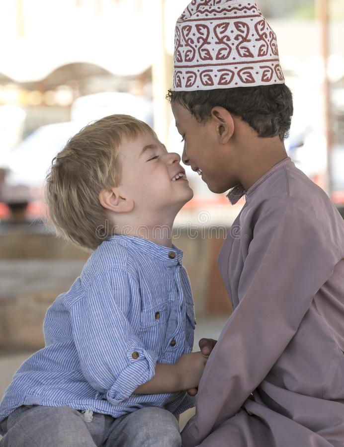 Omani jongen die frineds met Europese jongen maken stock afbeeldingen