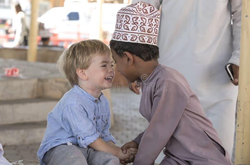 Omani jongen die vrienden met Europese jongen maken royalty-vrije stock foto