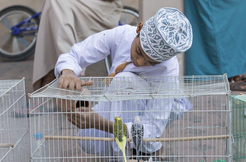 omani jongen met een vogelkooi stock afbeelding
