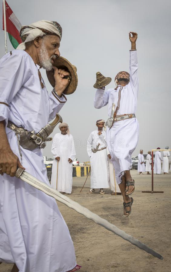 Omani man throwing a sword in a air to demonstrate his skill royalty free stock images