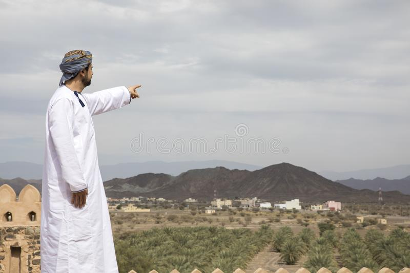 Arab man in traditional omani outfit pointing to the distance stock photography