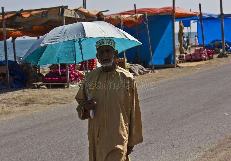 Omani man walking with the umbrella stock image