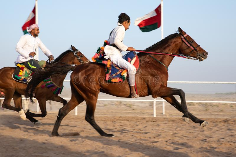 Omani men showing off their riding skills. stock images
