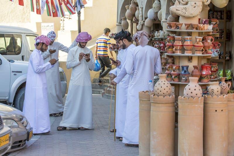 Omani mensen bij een markt, allen in hun het mobiele telefoons texting royalty-vrije stock fotografie