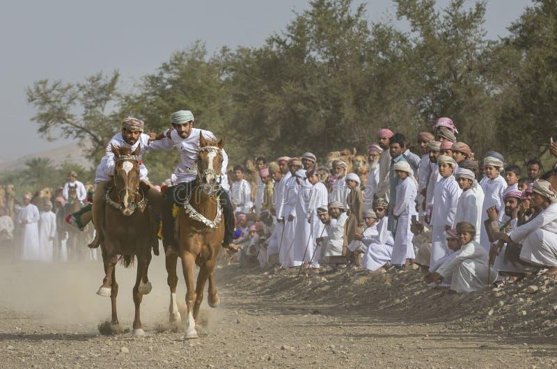 Omani mensen die paarden in landelijk Oman rennen stock foto