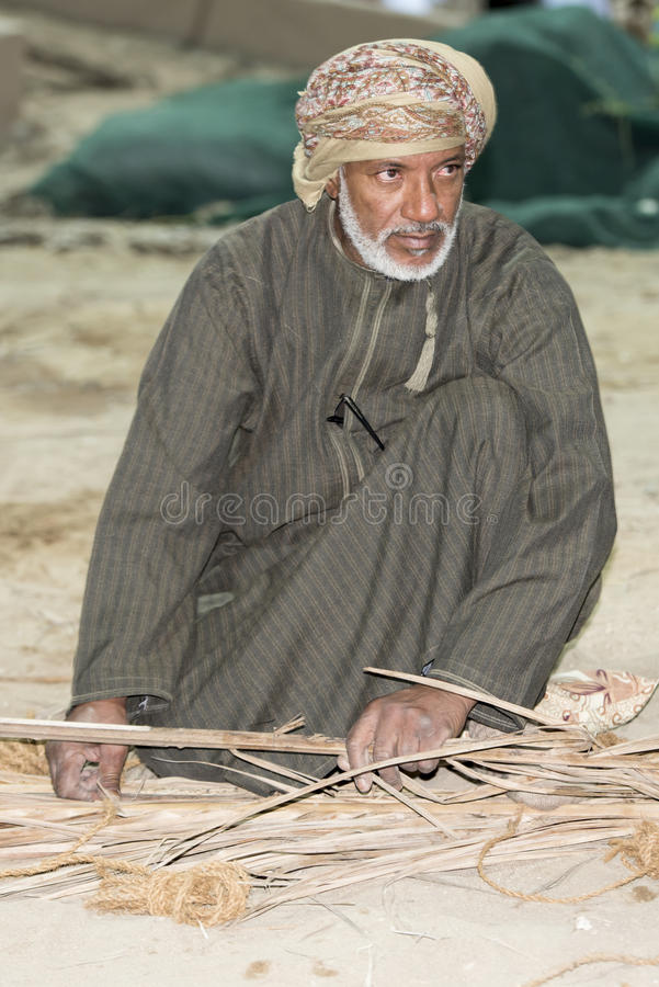 Omani man weaving palm leaves stock images