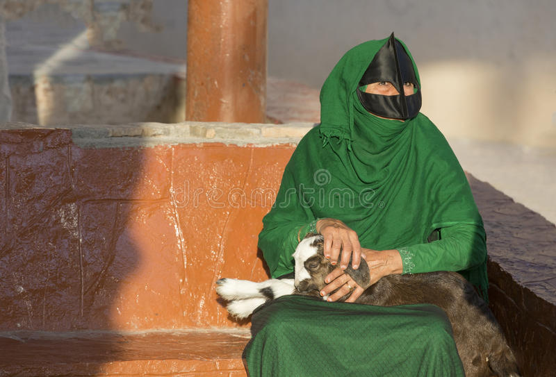Omani woman in a market with a baby goat stock image