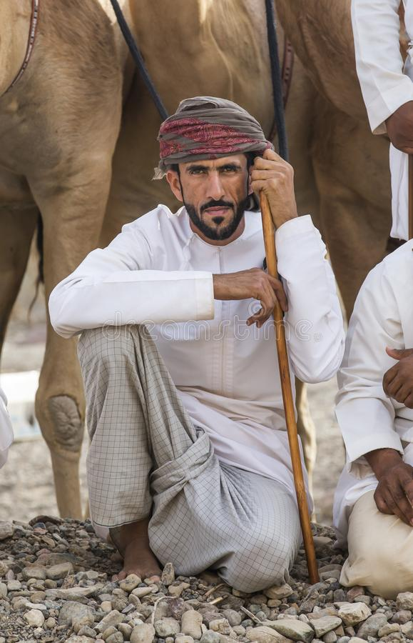 Omansk man med hans kamel för ett lopp royaltyfria bilder