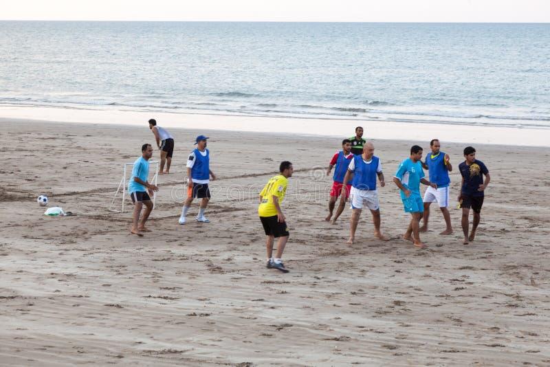 Omanska män som spelar fotboll på stranden i Muscat royaltyfri bild