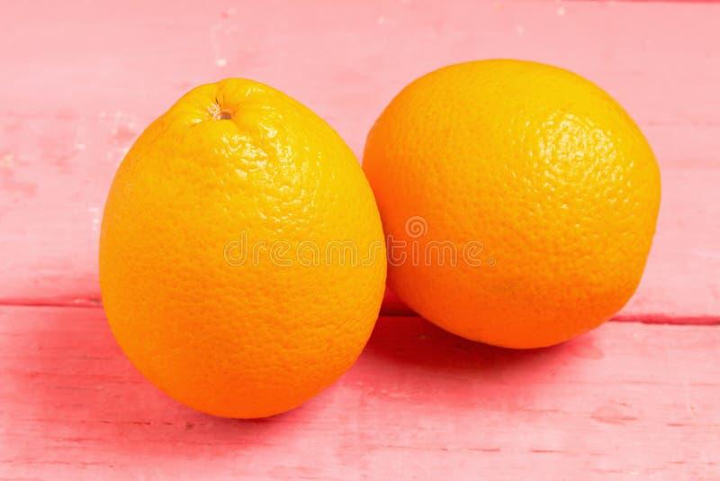Ombligo anaranjado de la fruta en la madera rosada imagenes de archivo