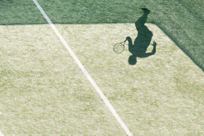 Ombra del razzo della tenuta del tennis sulla superficie di verde della corte fotografia stock