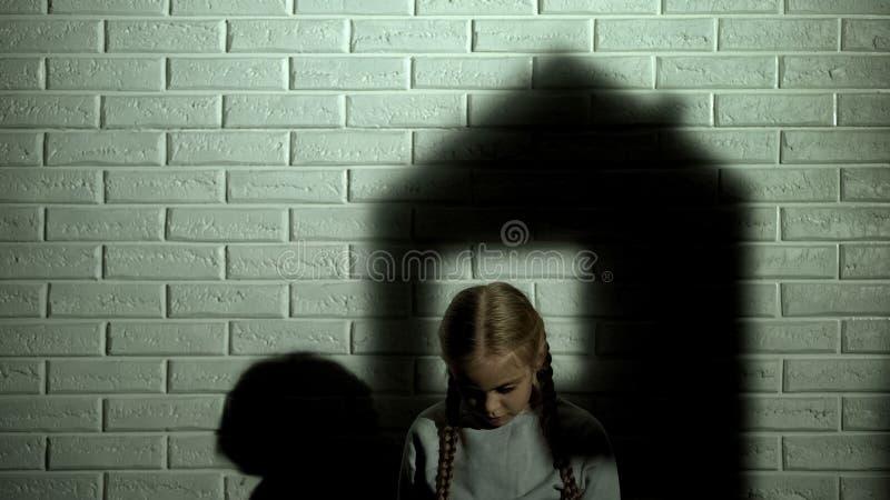 Ombra della Camera sulla parete dietro la bambina, i bisogni orfani del bambino a casa e la famiglia fotografie stock libere da diritti