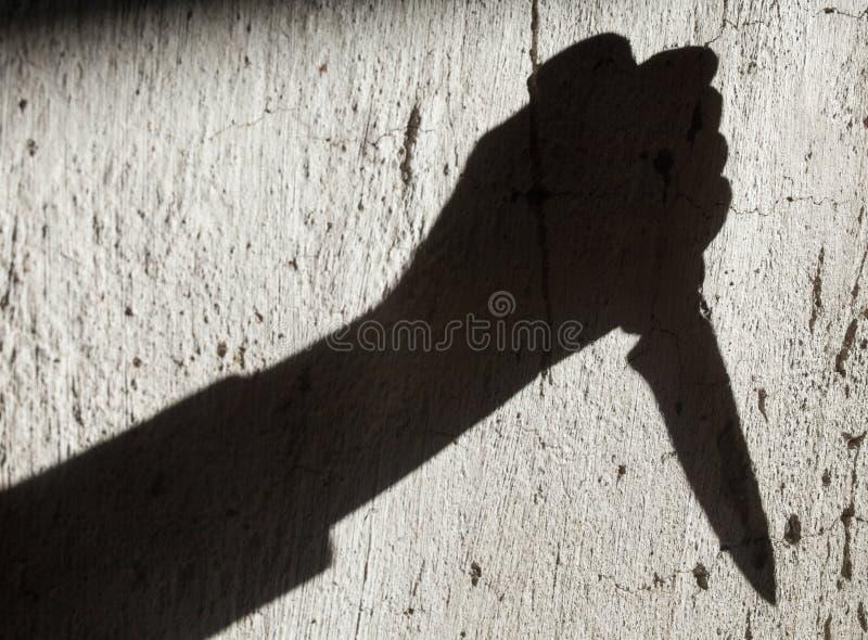 Ombra della mano che tiene un coltello fotografia stock