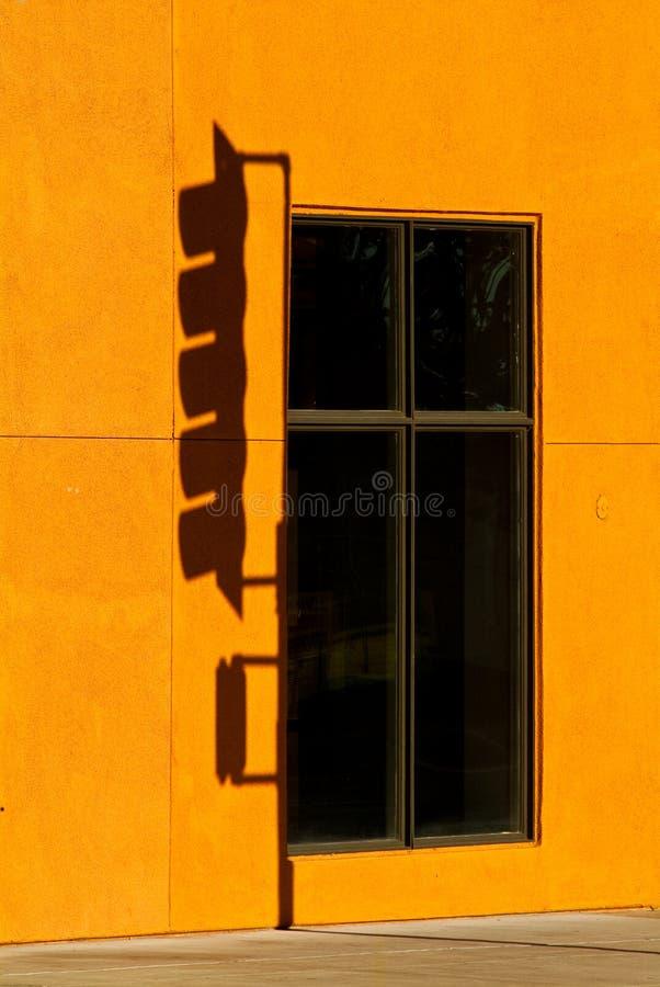 Ombra dello Stoplight contro la parete arancione fotografia stock
