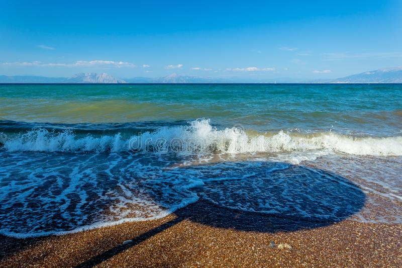 Ombra di un parasole in onde su un Pebble Beach greco fotografie stock