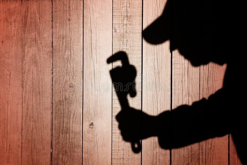Ombra di un uomo con la chiave su fondo di legno naturale immagini stock