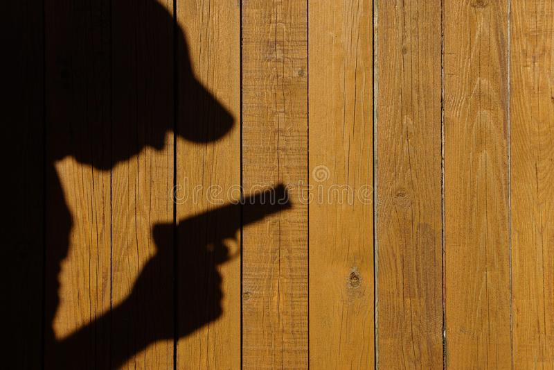 Ombra di un uomo con una pistola su un recinto di legno, immagine di XXXL fotografia stock libera da diritti