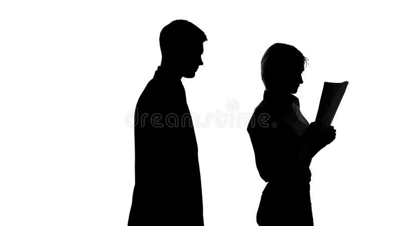 Ombra maschio che si avvicina al suo segretario che tiene i documenti, molestia sessuale fotografie stock libere da diritti