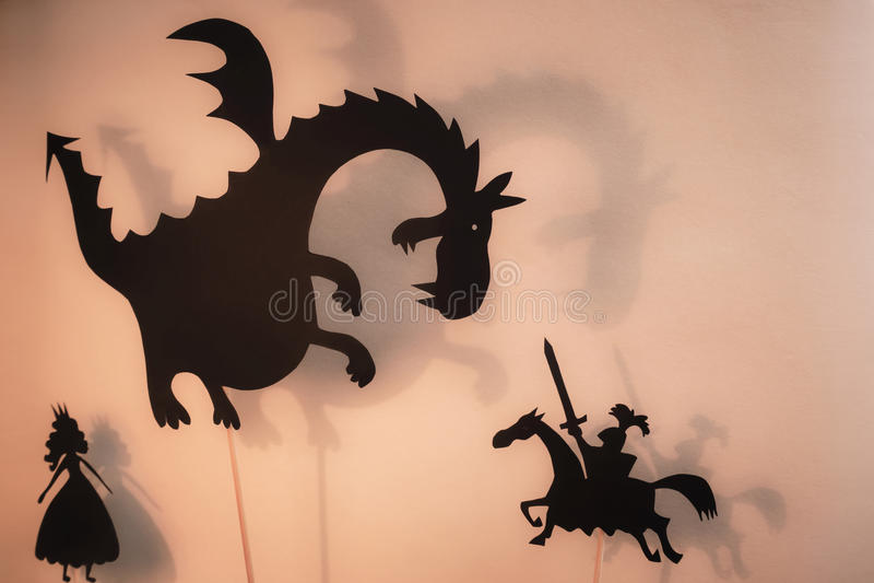 Ombragez les marionnettes du dragon, de la princesse et du chevalier avec l'écran rougeoyant lumineux du théâtre d'ombre à l'arri illustration stock