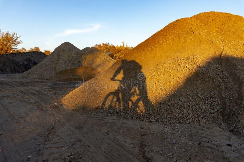 Ombre d'un homme poussant une bicyclette sur le gravier images libres de droits