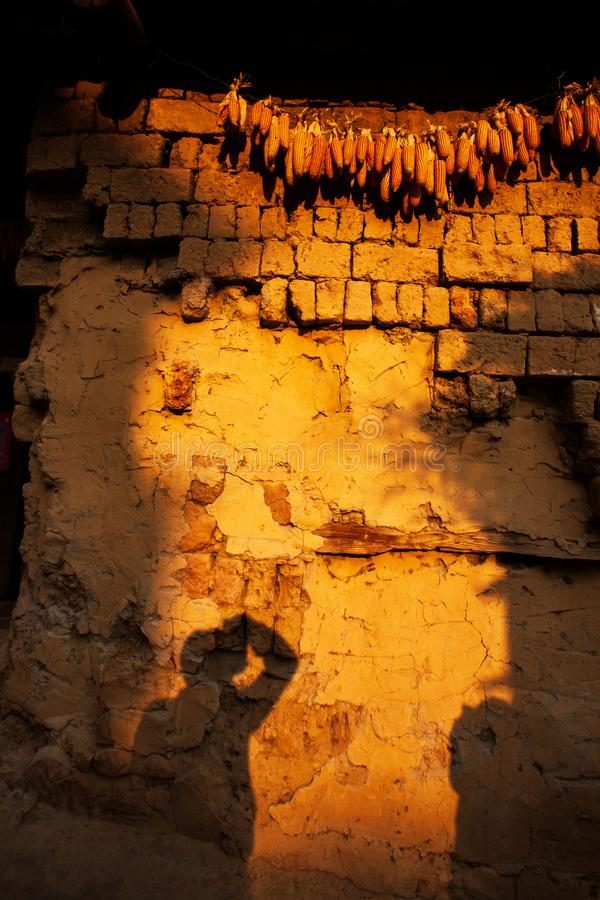 Ombre d'un photographe sur le mur de terre de la maison chinoise antique au crépuscule, village de Chengzi, Yunnan, Chine photographie stock