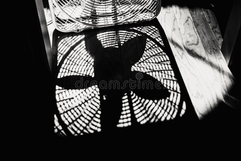 Ombre d'une fan de boîte sur un plancher en bois photo libre de droits