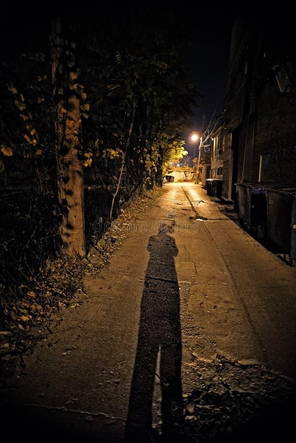 Ombre d'une personne dans une allée foncée de ville la nuit images libres de droits