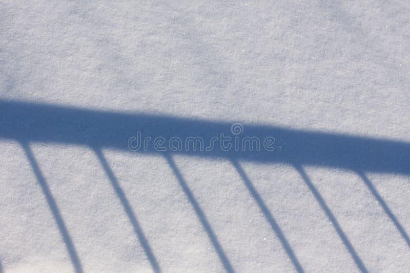 Ombre de la balustrade sur la neige images stock