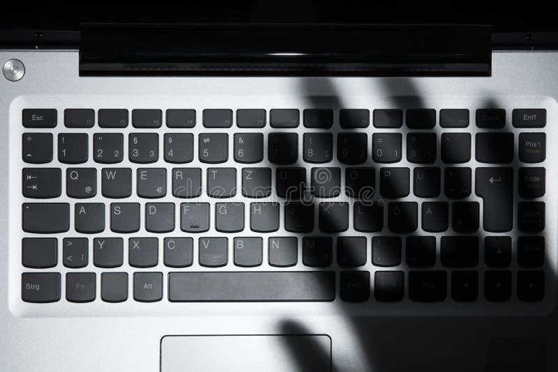 Ombre de la main du ` s de personne tombant sur le clavier numérique d'ordinateur portable images libres de droits