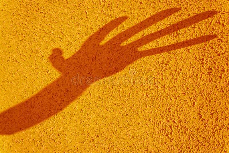 Ombre de main déformée sur le mur jaune texturisé photo stock