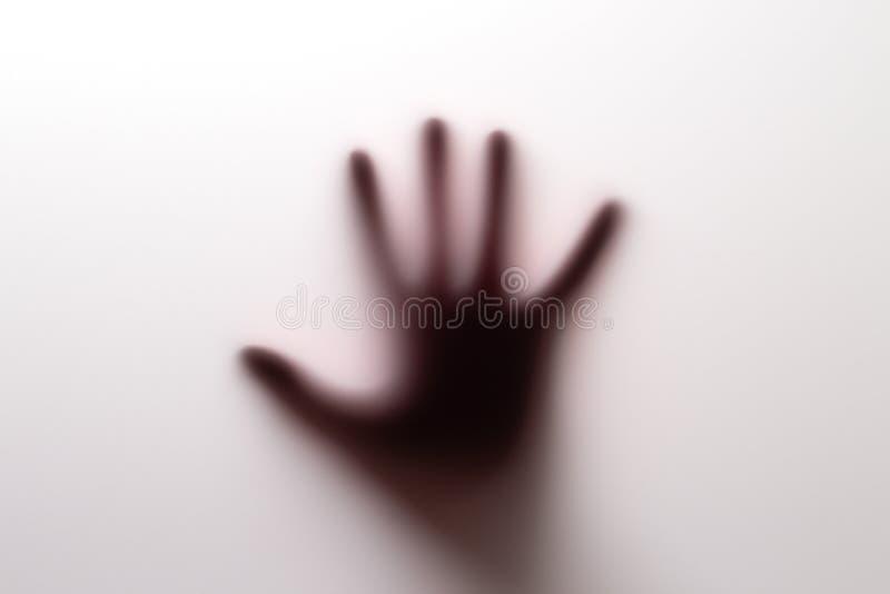 Ombre de main derrière le verre photo stock