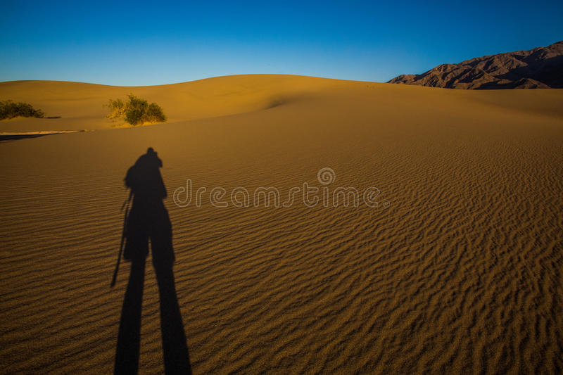 Ombre de photographe sur les dunes en parc national de Death Valley photographie stock
