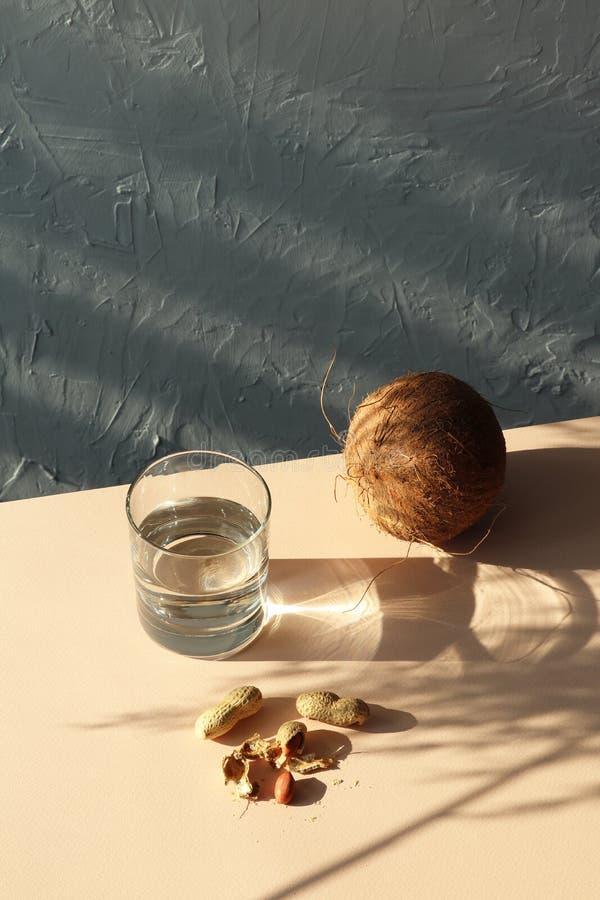 Ombre de Sun sur la table avec le verre de l'eau, noix de coco, arachide image libre de droits