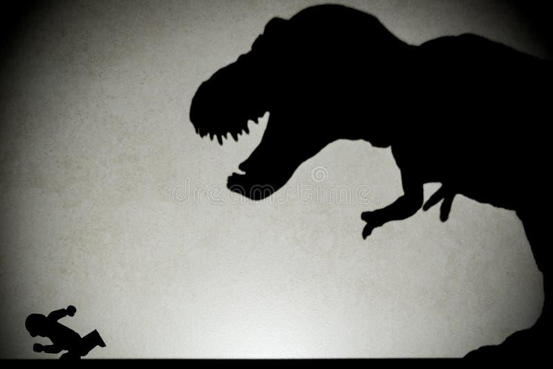 Ombre de tyrannosaure chassant l'humain sur le mur photographie stock