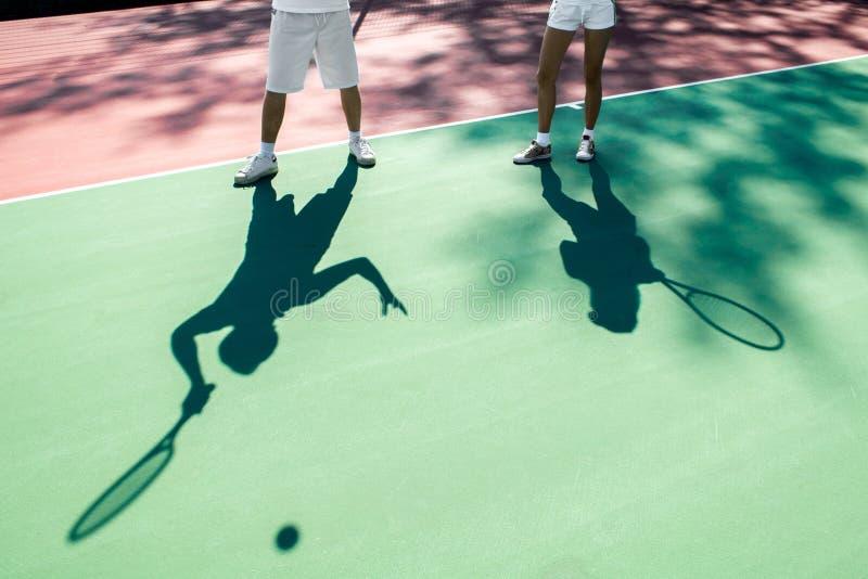 Ombre dei giocatori sul campo da tennis fotografia stock