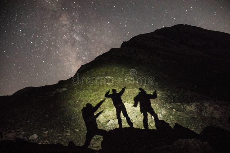 Ombre della gente nella montagna con la Via Lattea nella parte posteriore fotografia stock