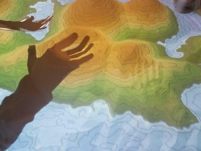 Ombre delle mani sulle colline della sabbia con le linee di contorno fotografie stock