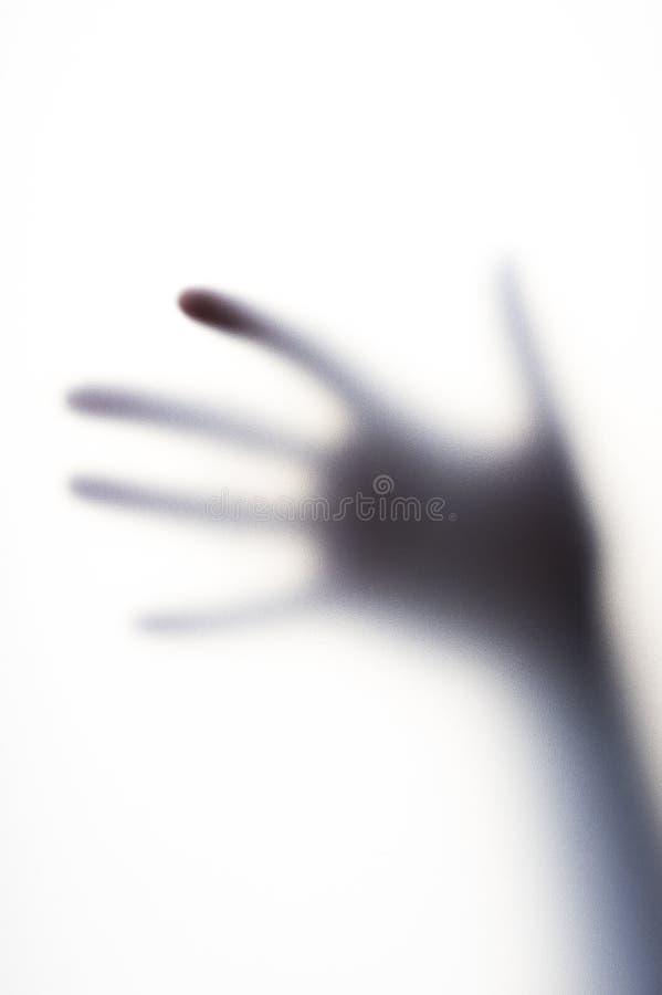 Ombre diffuse de main avec les doigts minces derrière le verre givré photographie stock